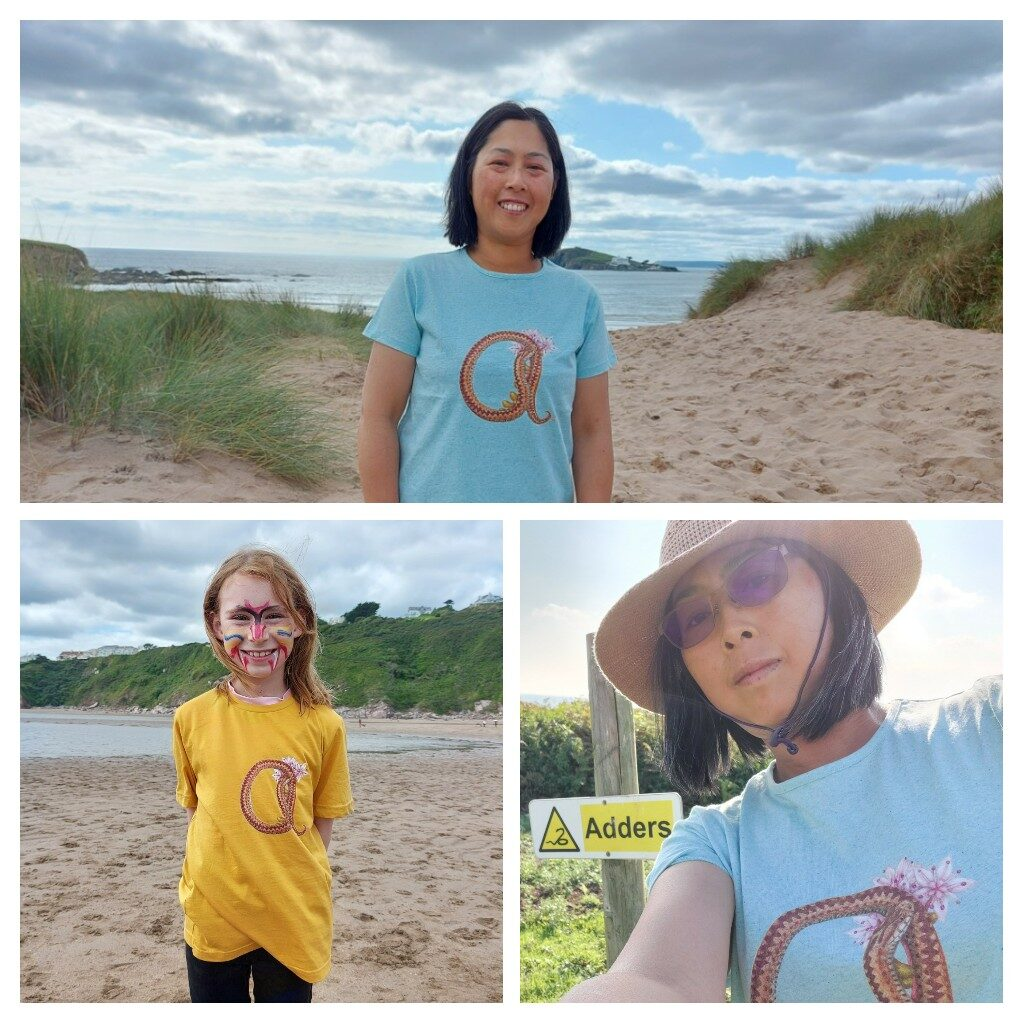 """Mabel wearing an """"a is for adder"""" light blue organic recycled t-shirt at Bantham.  Child wearing a mustard adder t-shirt.  Mabel next to a yellow and black """"Adder"""" sign."""